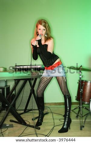 Caucasian female singing into microphone. - stock photo
