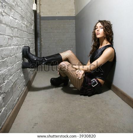 Caucasian female sitting in hallway. - stock photo