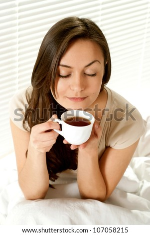 Caucasian female sitting on a bed with a cup on a light background