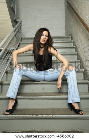 Caucasian female sitting on steps of stairwell. - stock photo