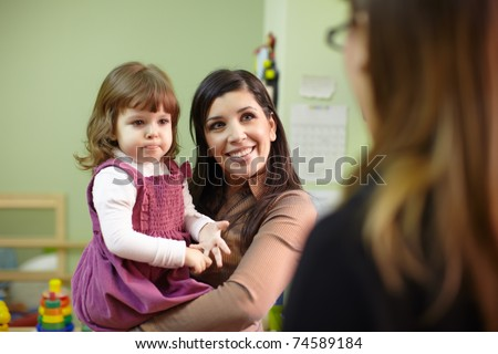 Caucasian female teacher and mom with baby girl talking in kindergarten. Horizontal shape, focus on background