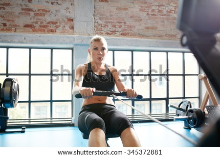 Caucasian female using rowing machine in the gym. Young woman doing cardio workout in fitness club. - stock photo