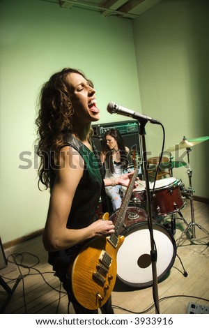Caucasian females singing into microphone and playing the drums. - stock photo