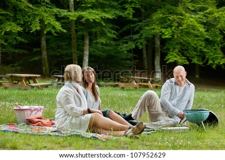 Caucasian friends relaxing at an outdoor picnic in forest park - stock photo