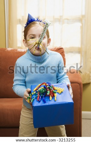 Caucasian girl blowing noisemaker and holding gift. - stock photo