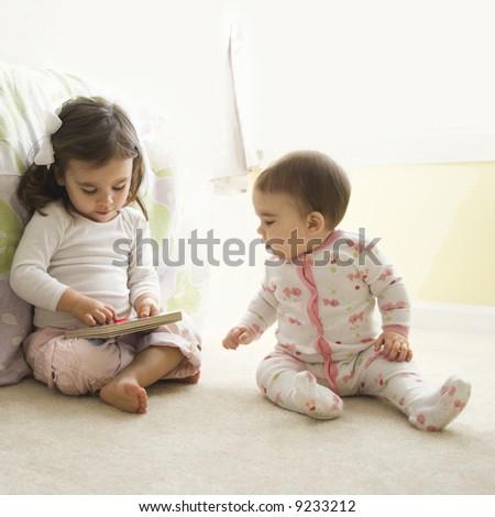 Caucasian girl children sitting on bedroom floor looking at book. - stock photo