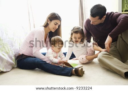 Caucasian girl children with mother and father sitting on bedroom floor looking at book. - stock photo