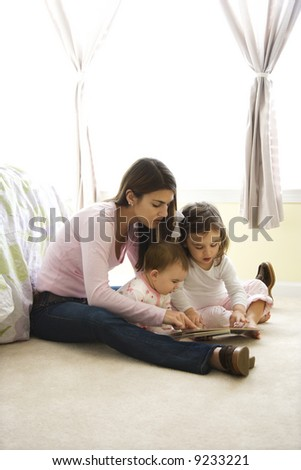Caucasian girl children with mother sitting on bedroom floor looking at book. - stock photo