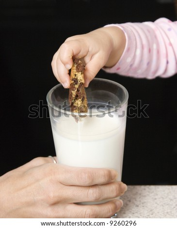 Caucasian girl dipping chocolate chip cookie into glass of milk. - stock photo