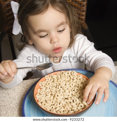 Caucasian girl eating bowl of cereal. - stock photo