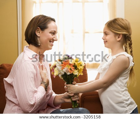 Caucasian girl giving mid adult mother a drawing. - stock photo