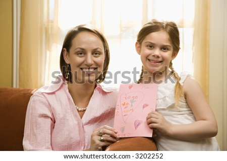 Caucasian girl giving mid adult mother a drawing and looking at viewer. - stock photo