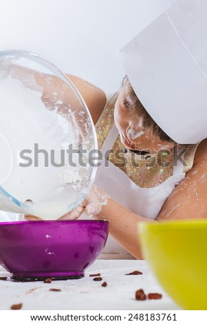 Caucasian girl making a cake, isolated on white background - stock photo