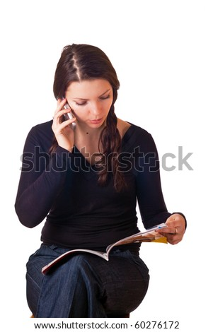 Caucasian girl reading magazine and talking by mobile phone. Isolated on white. - stock photo
