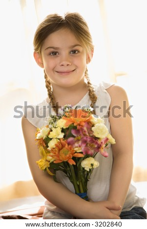 Caucasian girl smiling at viewer with bouquet of flowers. - stock photo