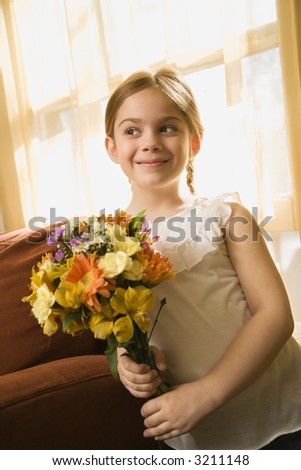 Caucasian girl smiling holding bouquet of flowers. - stock photo