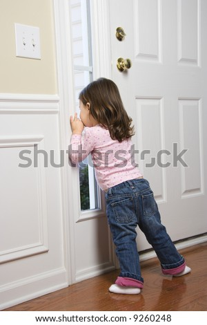 Caucasian girl toddler peeking out of window by door. - stock photo