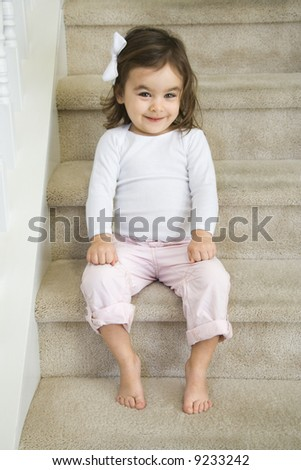Caucasian girl toddler sitting on carpeted stairs. - stock photo