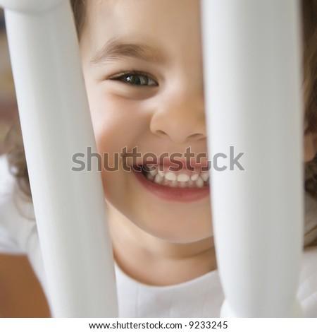 Caucasian girl toddler smiling and peering between railing. - stock photo