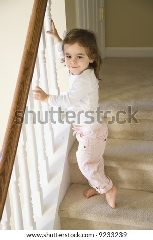 Caucasian girl toddler standing on carpeted stairs holding onto railing.