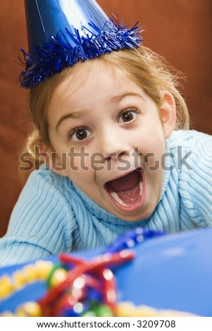 Caucasian girl wearing party hat holding gift  and looking at viewer with excited expression. - stock photo