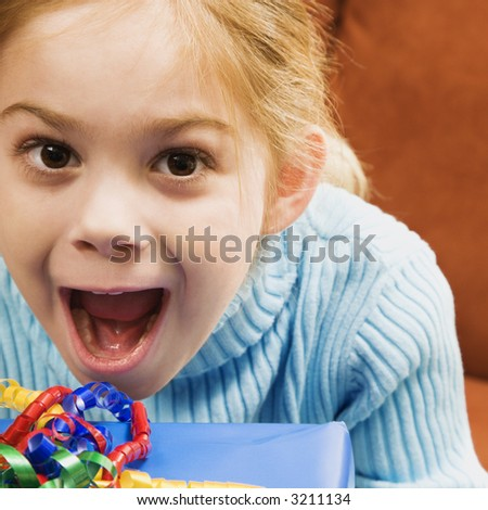 Caucasian girl with excited expression looking at viewer. - stock photo