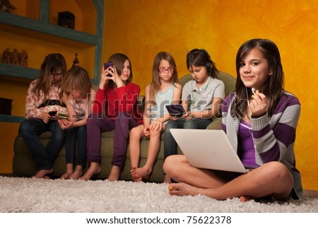 Caucasian girl with laptop while friends are busy with handheld devices - stock photo