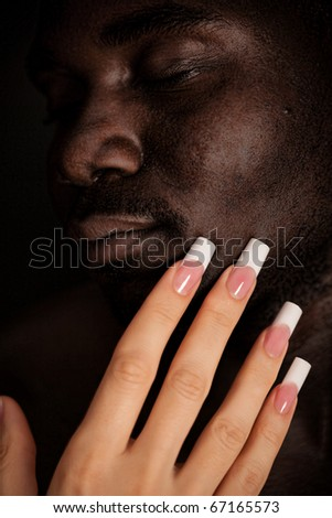 Caucasian girl with long manicure touch the face of a black man - stock photo