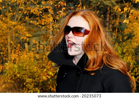 Caucasian girl with long red hair and sunglasses in autumn colored forest - stock photo