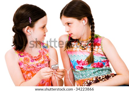 Caucasian girls listening to MP3 player isolated over white - stock photo