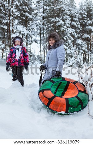 Caucasian grandmother and daughter going for a walk, riding on an inflatable tube from slides - stock photo