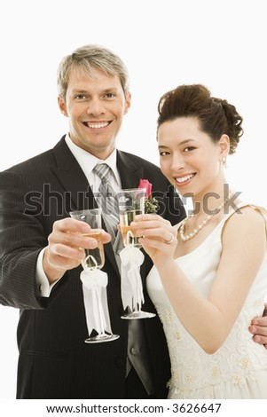 Caucasian groom and Asian bride toasting with champagne glasses.