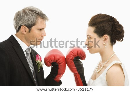 Caucasian groom and Asian bride wearing boxing gloves. - stock photo
