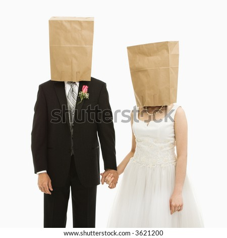 Caucasian groom and Asian bride with brown paper bags over their heads. - stock photo
