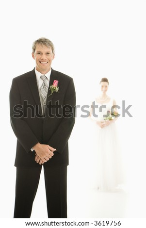 Caucasian groom in foreground and Asian bride in background. - stock photo