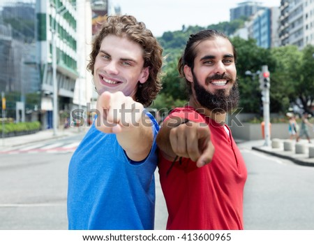Caucasian guy with arabian friend pointing at camera thumb in the city - stock photo