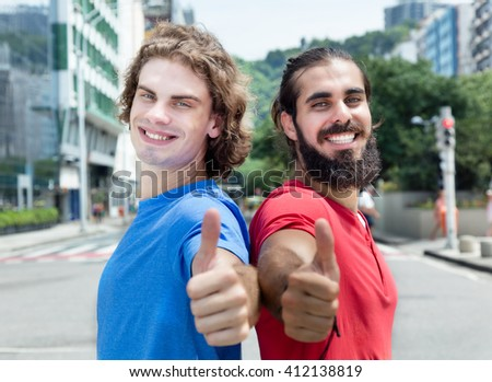Caucasian guy with arabian friend showing thumb - stock photo