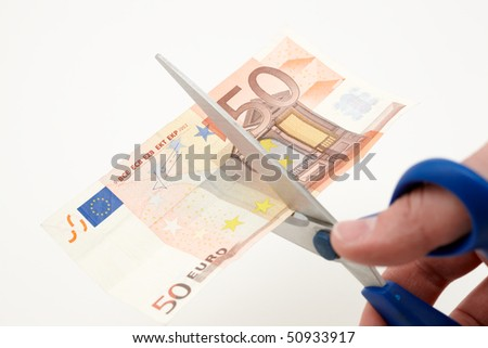 caucasian hand cutting a banknote with scissors - stock photo