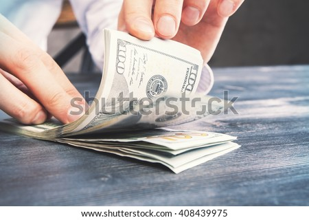 Caucasian hands counting dollar bills on darw wooden table - stock photo
