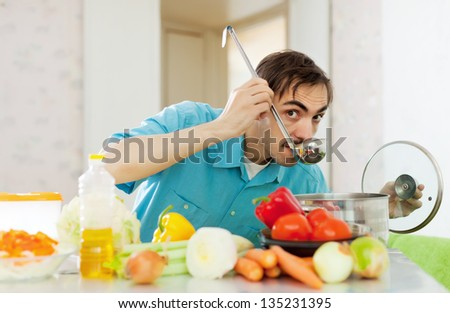 Caucasian handsome man tasting veggie soup with ladle from pan in kitchen - stock photo