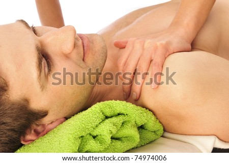 Caucasian handsome spa man getting wellbeing massage laying on green towel. Copyspace - stock photo