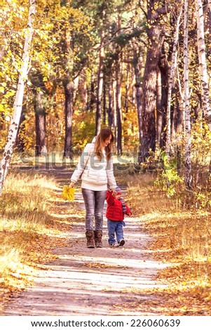 Caucasian happy family (mother and son) are walking on path (pathway) in the autumnal park. Relaxing young woman and her toddler boy are in the sunny day. - stock photo