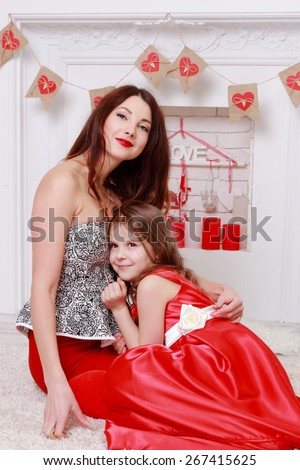 Caucasian happy mother and her daughter spending time together over charming interior on Holiday theme - stock photo