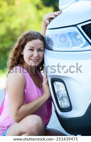 Caucasian happy woman sitting near own new vehicle - stock photo