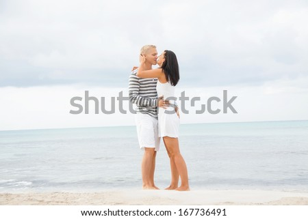 Caucasian happy young couple holding hands while walking barefoot on the beach in a romantic travel destination - stock photo