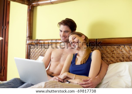 caucasian heterosexual couple watching movie on laptop computer in bedroom. Horizontal shape, three quarter length, side view - stock photo