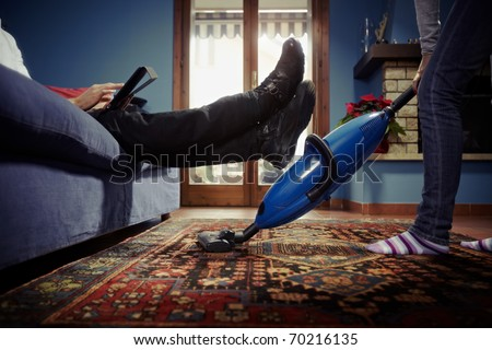 caucasian heterosexual couple, with woman doing chores using vacuum cleaner on carpet and lazy man on sofa with tablet pc. Horizontal shape, low angle view - stock photo