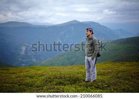 Caucasian hiker on a pasture in the mountains - stock photo