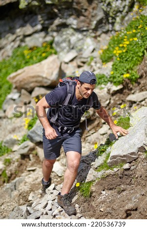 Caucasian hiker with backpack hiking into the mountains - stock photo
