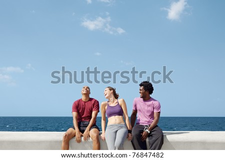 caucasian, hispanic and african american friends smiling and having fun near the sea. Horizontal shape, three quarter length, copy space - stock photo